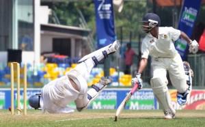 Thurstan batsman Charana Nanayakkara makes it to the crease on time to beat Isipathana wicketkeeper Kavindu Kulasekara who makes an acrobatic attempt for a run out.   - Pic by Amila Gamage