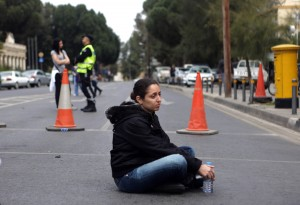 A Cyprus bank employee sits on the ground as protesters blocked the streets leading to the parliament in Nicosia.  AFP