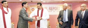 Economy doing well: Central Bank Governor Nivard Cabraal formally hands over the Central Bank Annual report 2012 to President Rajapaksa