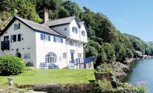 "The house she loved (top) and (right) Daphne du Maurier rowing across Fowey estuary to ""Ferryside'"