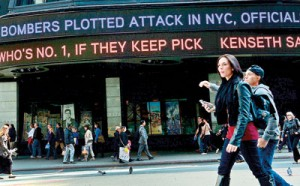 People walk by news ticker announcing on April 25, 2013, that bombers in the Boston marathon were plotting attacks on New York City's Times Square in New York (AFP/Emmanuel Dunand)
