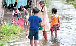 Flooded out: Children in the shanty dwellings on Nuga Road in Wanawasala