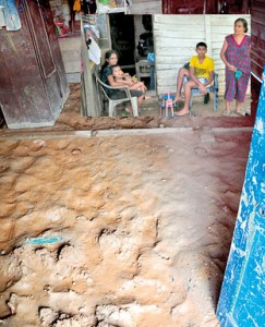 Razline and her family (incet) wait outside their humble abode that was filled with flood waters and mud