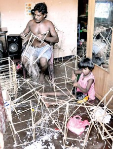 It's a family affair: This little girl helps her father to make lantern frames