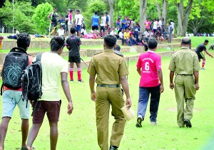 Incidents like this happen elsewhere other than in the rugby grounds: Two policemen are seen escorting out two players and a team official after they were accused of verbally abusing a match official at the 46th Junior National Hockey tournament yesterday. - Pic by Amila Gamage.