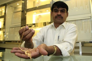 A salesman at a local store displays a necklace. Pic. by Indika Handuwala