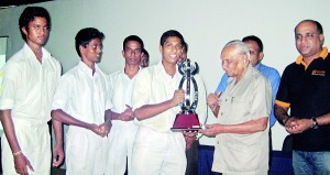 Pictured here is the captain of Ananda College's team receiving the trophy from Edwin Ariyadasa.