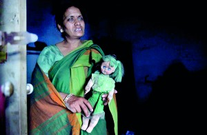 Sarita Gupta, 51, a yoga teacher, holds a doll belonging to her missing fifteen-year-old daughter Ambika inside her house in New Delhi (REUTERS)