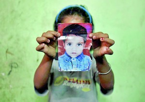 Mansi, 7, poses with a photograph of her missing three-year-old sister, Muskaan, inside their house in New Delhi (REUTERS)