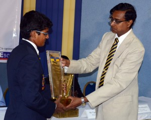Royal College hockey captain Shahid Hussain officially hands over the Blue and Gold Trophy to his principal Upali Gunasekara. - Pic by Hasitha Kulasekara