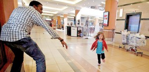 Their story: Portia Walton runs for the safety of Kenya mall hero Abdul Haji. The Waltons have now shared their harrowing tale, giving backstory to this now-iconic photo (Reuters)
