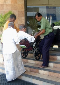 An elderly shareholder being given a helping hand to attend the AGM. Pic by Nilan Maligaspe.