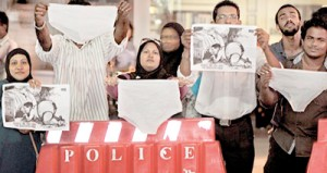 Male, MALDIVES: Maldivian activists wave underwear and cartoons as they stage a protest in Male on September 26. AFP PHOTO