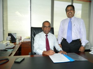 """Picture shows Director/CEO of Pan Asia Bank Claude Peiris signing the agreement on behalf of the bank, flanked by Richie Dias, DGM-Treasury"""""""