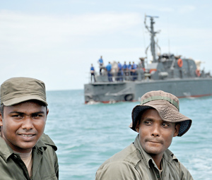 The two Special Boat Squadran men who steered the flat bottom fibre glass boat that took the Sunday Times team to Kachchativu seen in the foreground, while the Dvora that brought the team to mid sea is seen in the background