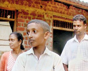 The boy with his parents. Pic by Kanchana Kumara Ariyadasa