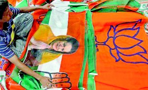A worker looks at a Congress party flag carrying a picture of its party chief Sonia Gandhi next to flags of main opposition Bharatiya Janata Party (BJP) inside an election campaigning material workshop on the outskirts of Ahmedabad (Reuters)