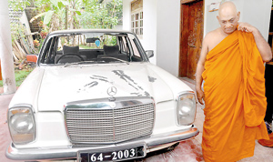 The chief monk stands besides one of the damaged vehicles