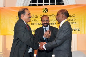 Picture shows the newly elected Chairman of the CNCI, Gamini Gunasekara  being greeted by outgoing Chairman  Preethi Jayawardena (left) in the presence of Secretary to the Ministry of Industry and Commerce, Anura Siriwardena.