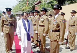 Governor Tikiri Kobbekaduwa inspects the guard of honour with the Officer-in-Charge of the Balagolla police