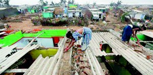 Women repair the roof of their houses at the cyclone-hit Nalianuagaon village in Ganjam district in Odisha (REUTERS)