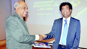 The author presenting a copy of book to the Attorney General Palitha Fernando.  Pic by Ranjith Perera