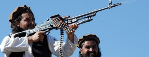 This AFP file picture taken on November 26, 2008, shows  Hakimullah Mehsud (L) firing from a rifle as he poses for journalists in the Mamouzai area of Orakzai Agency.