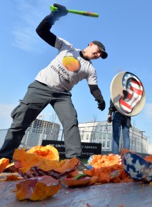 "A Ukrainian activist wearing a T-shirt reading ""I hear everything !"" breaks Halloween pumpkins painted with the colours of the American flag and mounted with headphones, as another activist holds a sign made from a satellite dish with an ear painted in the colours of the American flag, as they protest  on Friday in Kiev over US surveillance of European citizens. AFP"