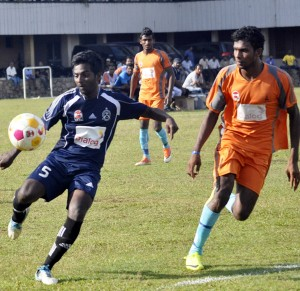 A Nandimithra (blue) player clears the ball. Pic by Susantha Liyanawatte
