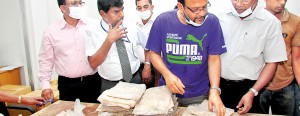 Custom officials inspect the packets of heroin found in the cans of grease (above) that arrived in a consignment from Pakistan