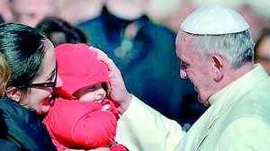 Pope Francis blesses a baby during his general audience in St Peter's Square  (AFP)