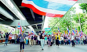 Thai anti-government protesters wave national flags as they march through the streets of Bangkok as part of their ongoing rally on December 20 (AFP)