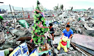 A typhoon Haiyan survivor decorates a Christmas tree amid the rubble of destroyed houses in the City of Tacloban in central Philippines (Reuters)