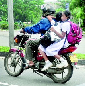 At risk to life and limb parents are forced to take two or more children on the pillion of their bikes.