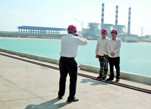 Cheese: Chinese workers snap a picture with the power station as backdrop