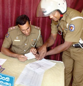 Police officers  studying the forged items. Pix by Suranga Rajanayaka