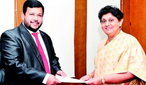 Picture shows the Minister handing over the appointment letter to Mrs. Suganthie Kadirgamar.