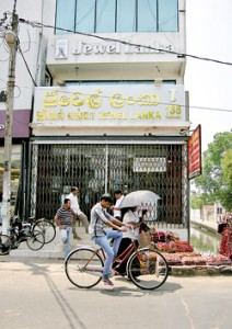 Wearing full-face helmets, robbers got away easily with two bags filled with foreign currency and jewellery  removed from this jewellery shop in Negombo town. Pic by Athula Devapriya