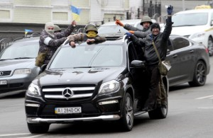 Anti-government protesters gesture as they stand on a car in the center of Kiev on February 22. The regime of Ukraine's president appeared close to collapse on February 22 as the emboldened opposition took control of central Kiev and key government and parliament positions and voted to immediately free its jailed leader Yulia Tymoshenko (AFP)