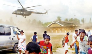 Children and adults alike flee to avoid the 'dust storm' raised by an incoming helicopter