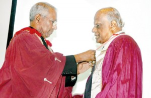 Dr Palitha Abeykoon (right) being inducted as the SLMA president by Dr B.J.C.Perera. Pix by Indika Handuwala