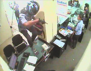 A CCTV grab shows the armed robber wearing full-face helmet jumping over a desk prior to removing the cash from the drawyers at the Kohuwala Nations Trust Bank