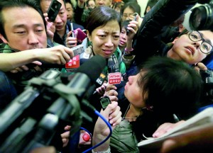A woman, whose husband is a passenger of Malaysia Airlines flight MH370, complains about Malaysia Airlines to journalists as she attempts to leave a hotel in Beijing, March 8, 2014. The flight carrying 227 passengers and 12 crew went missing over the South China Sea today presumed crashed, as ships from countries closest to its flight path scoured a large search area for any wreckage (REUTERS)
