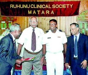 SLMA's 2013 President Dr. B.J.C. Perera receives the Guidelines from Dr. Malik Fernando in November last year, while Surgeon Lieutenant Dr. Buddhika Lokugamhewa who represented the Navy's Director-General of Health Services and Consultant Neurologist Dr. P.J.P. Peiris look on.