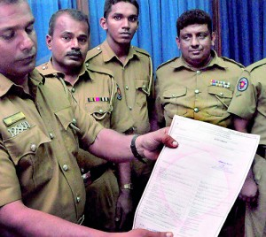 Police officers hold up a forged certificate of registration (inset). Pix by Mangala Weerasekera