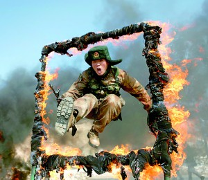 This picture taken on March 5, 2014 shows a soldier jumping over a ring of fire during a tactical training mission in Heihe, northeast China's Heilongjiang province. The latest double-digit increase to China's defence budget serves world peace and is no threat to anyone, state media argued (AFP)