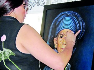 The artist gives expression to the portrait of a Burmese Kayan woman