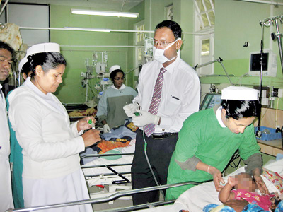 Consultant Virologist Dr. JudeJayamaha collects samples at the Nuwara Eliya Hospital in 2014. Inset left: The Respiratory Syncytial Virus highlighted in green
