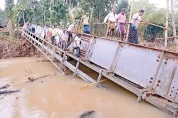 Flood victims risk lives on overturned bridge
