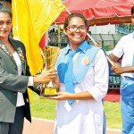 Sprinter Nadeeshani Handerson, the chief guest handing over the overall trophy to Peter House captain